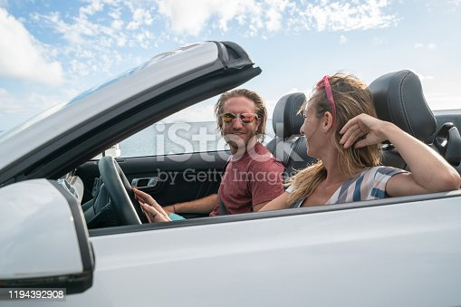 1030408008 istock photo Cheerful young couple inside convertible car enjoying vacations. Road trip concept.Oahu Island, Hawaii 1194392908