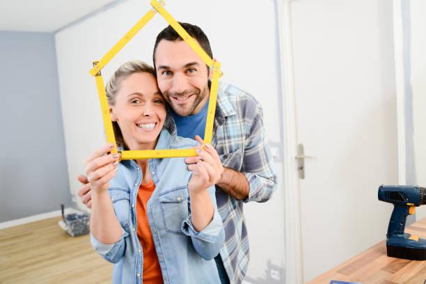 fröhliches junges paar zukunftsprojekt zu machen und neue wohnung renovieren - französisches haus dekor stock-fotos und bilder