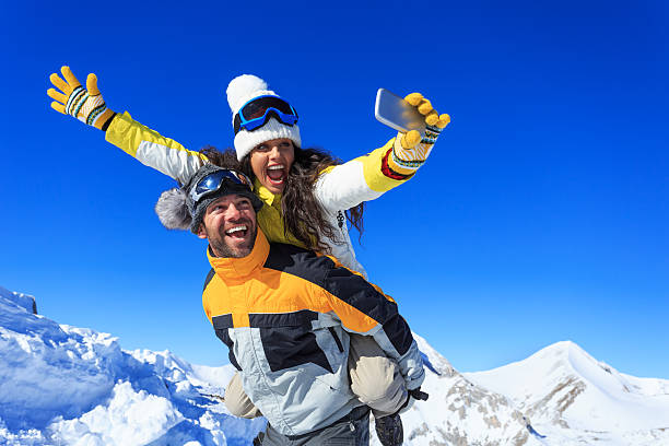 Cheerful young couple making winter selfie Cheerful young couple hikers making winter selfie on top of the mountain. Both wears warm clothes and gloves, knit hats and sunglasses. Woman in piggyback ride holding the smart phone. Mountain peak and clear sky on background. ski holiday stock pictures, royalty-free photos & images