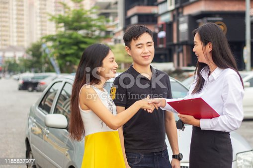 1178695243 istock photo Cheerful Young couple Meeting With Salesperson buying a new car 1185837977