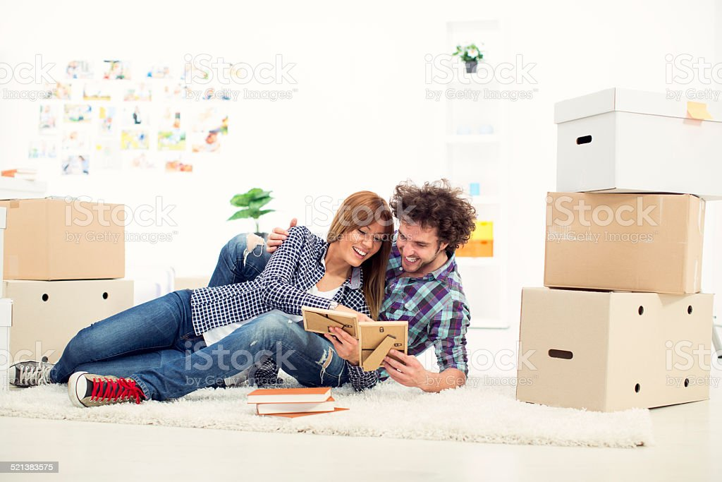 Cheerful young couple moving to new apartment. stock photo