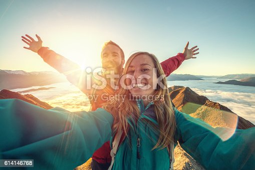 istock Cheerful young couple on mountain top take selfie 614146768