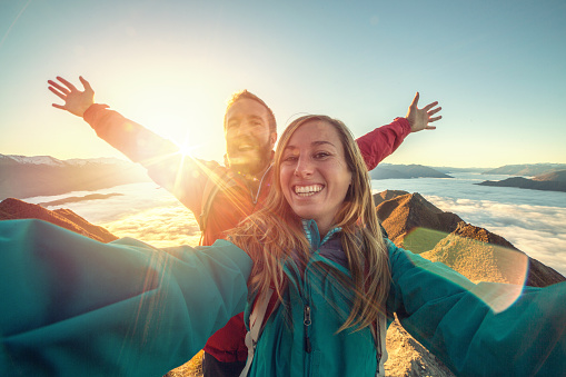 Young couple hiking stand on a mountain peak above the clouds and take a selfie portrait, sun shining over the mountains. Beautiful sunbeam effect making an idyllic landscape.