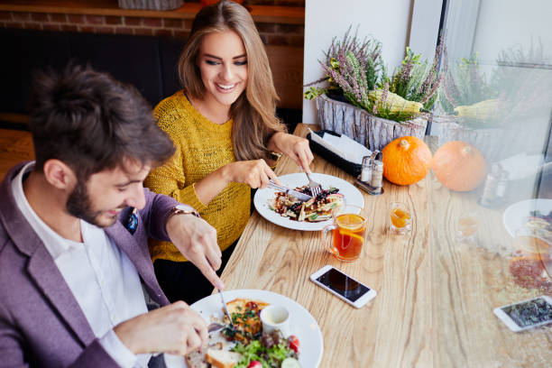 A cheerful young couple out for breakfast in a cafe before work stock photo
