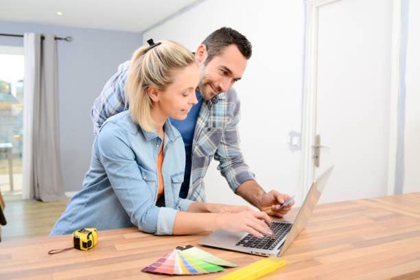 fröhliches junges paar renovieren wohndesign und auswahl von farben malen und möbel im internet mit einem laptopcomputer - französisches haus dekor stock-fotos und bilder