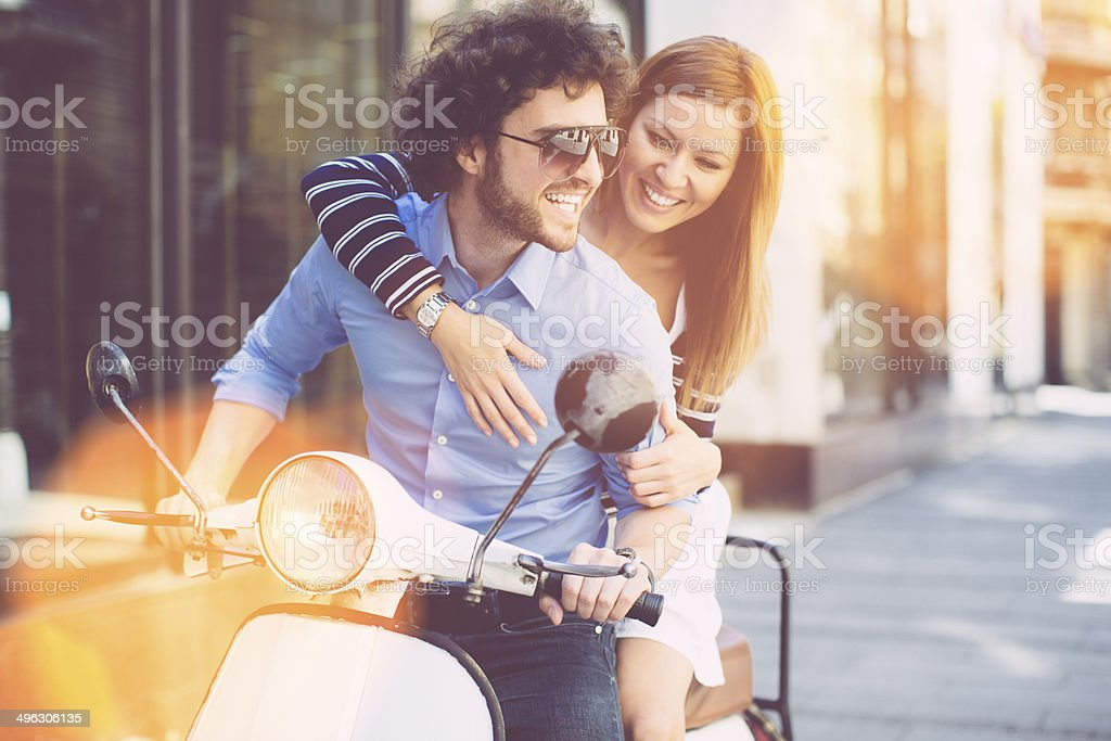 Cheerful Young Couple Riding on a motorbike. stock photo