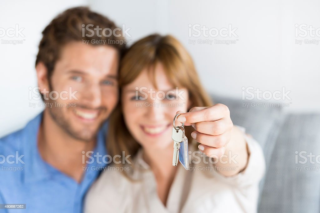Cheerful young couple showing  keys of their new apartment stock photo