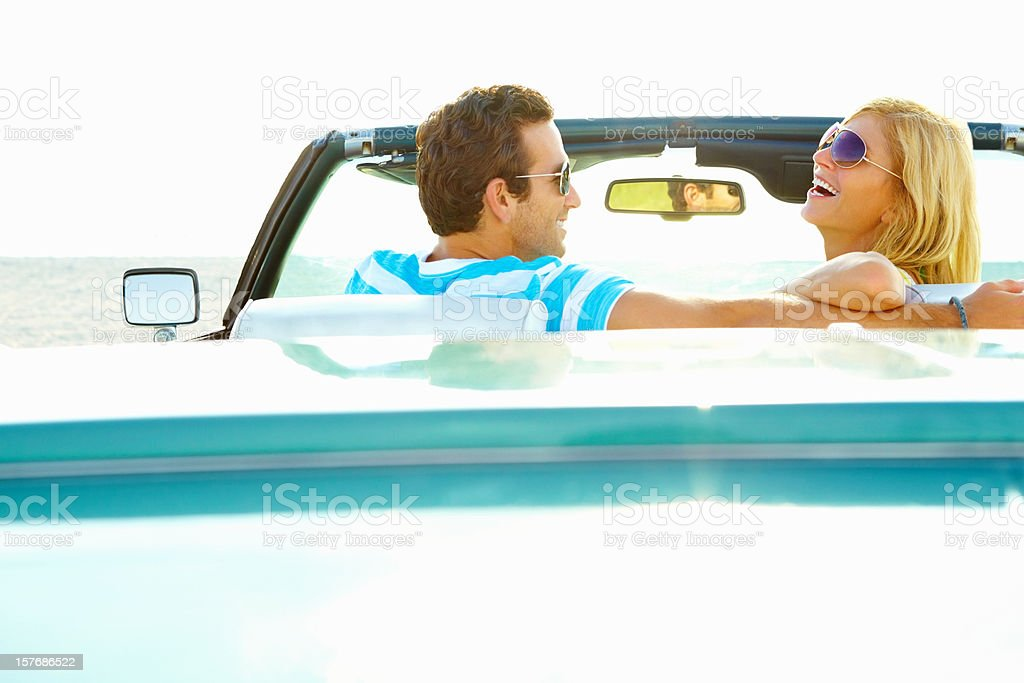 Cheerful young couple sitting in a convertible car royalty-free stock photo