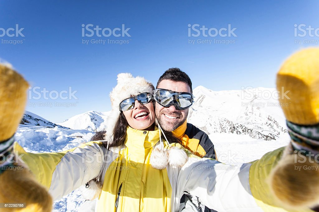 Cheerful young couple skiers making selfie in the snow mountain – Foto