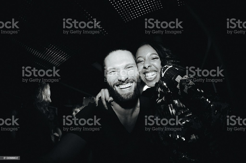 Cheerful young couple taking fanny selfie at club party stock photo