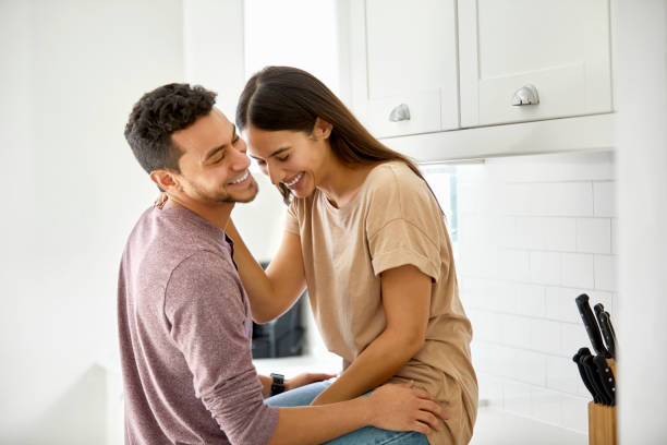 Fröhliches junges Paar sprechen in der Küche zu Hause – Foto
