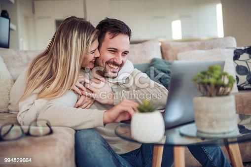Cheerful young couple using laptop together at home.