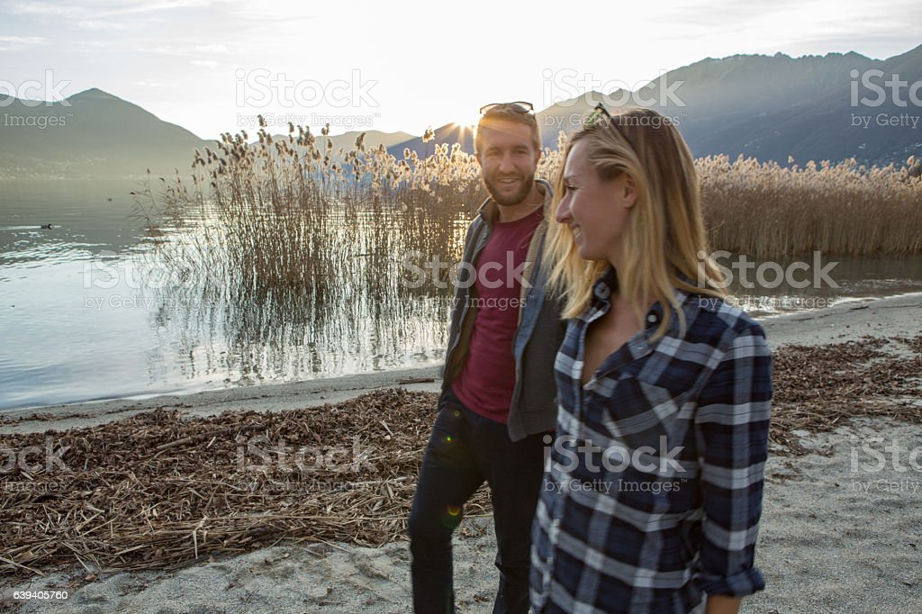 Cheerful young couple walking by the lakeshore at sunset stock photo