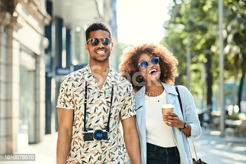 Cheerful young couple walking on sidewalk. Male and female hipsters are with camera and disposable coffee cup traveling in city. They are wearing casuals.