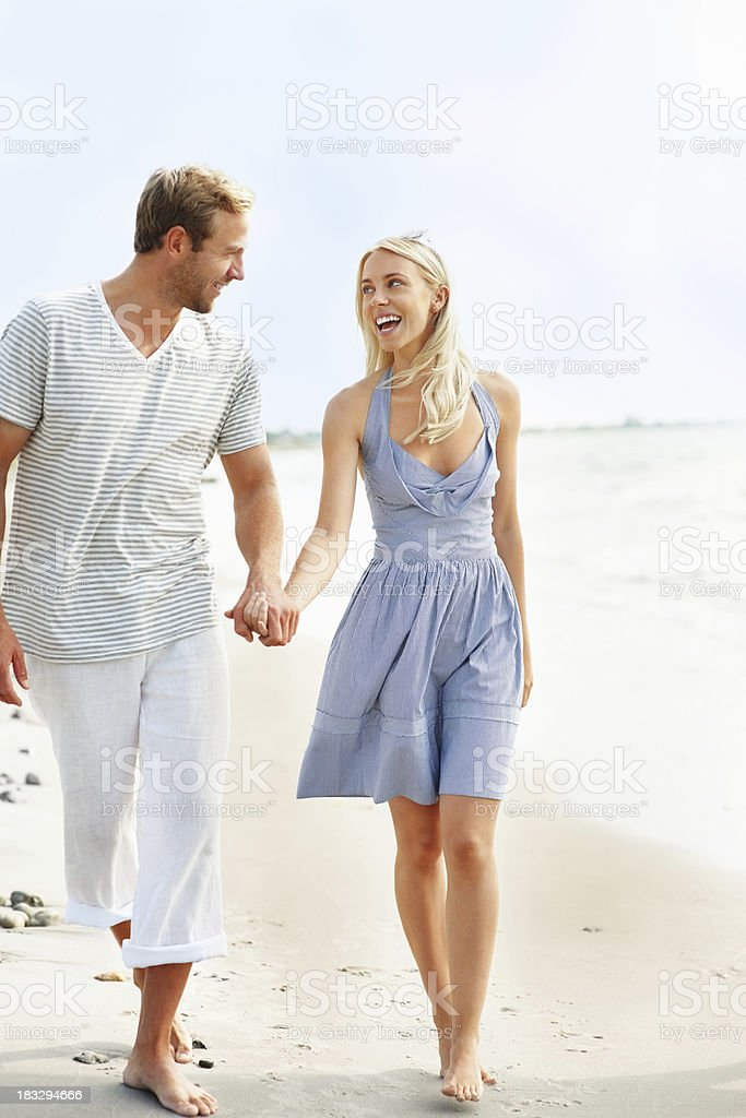 Cheerful, young couple walking on the beach, holding hands stock photo