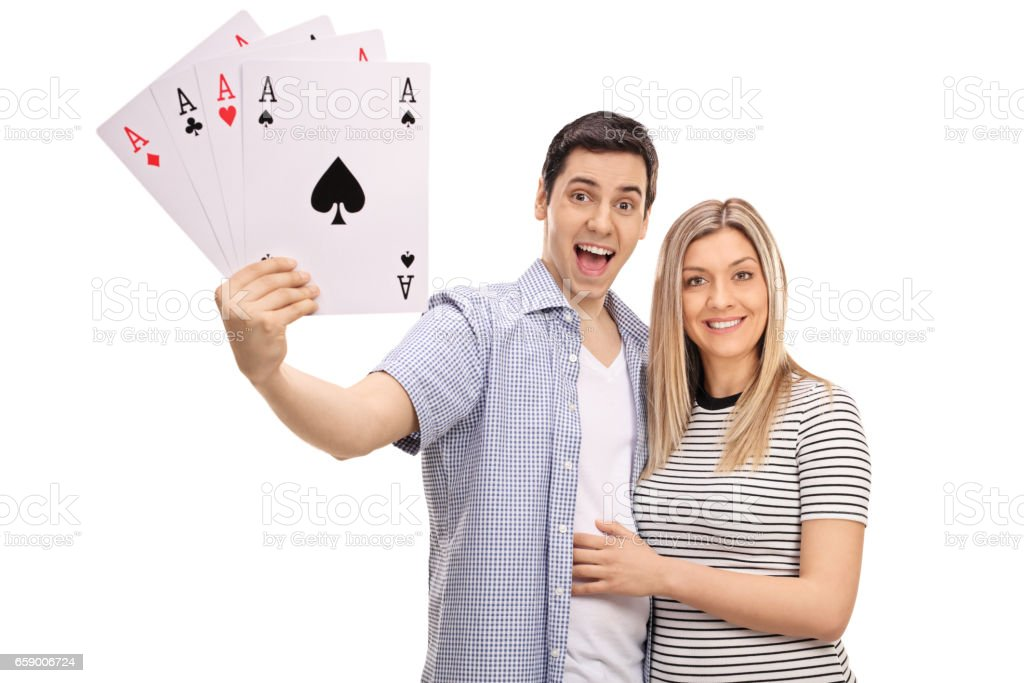 Cheerful young couple with four aces playing cards royalty-free stock photo