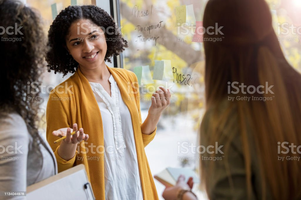 An excited young woman stands next to a window with unrecognizable...