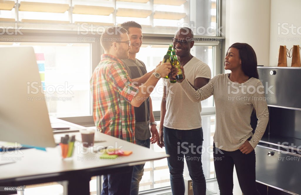 Cheerful young entrepreneurs relaxing with beer - foto stock