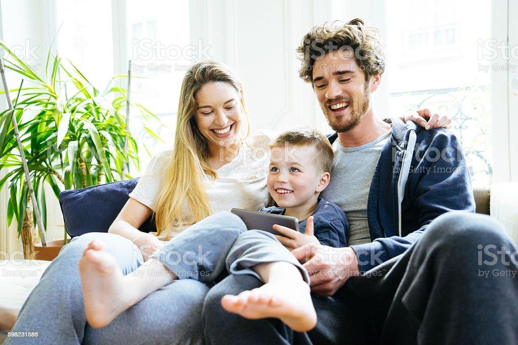 Alegre jovem família olhando no Tablet Digital em foto royalty-free