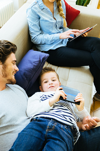 871175856 istock photo Cheerful Young Family Using Technology Together In The Living Room 614304286