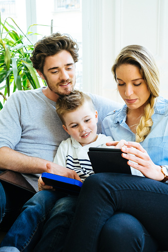 871175856 istock photo Cheerful Young Family Using Technology Together In The Living Room 639855498