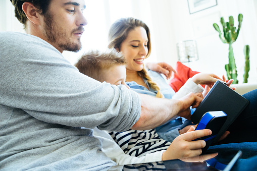 871175856 istock photo Cheerful Young Family Using Technology Together In The Living Room 640257808