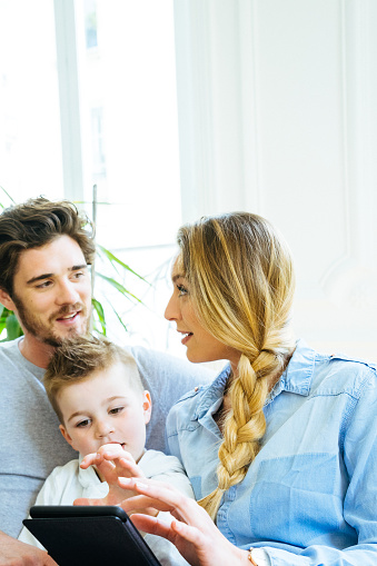 871175856 istock photo Cheerful Young Family Using Technology Together In The Living Room 640286636