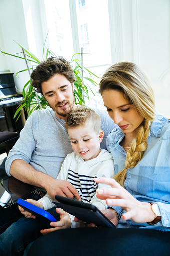 871175856 istock photo Cheerful Young Family Using Technology Together In The Living Room 640287080