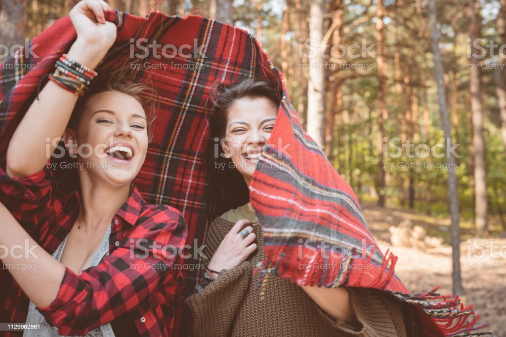 Cheerful young female friends holding in blanket Portrait of cheerful female hipsters holding red blanket. Beautiful young women are in forest. They are spending summer vacation. 20-24 Years Stock Photo