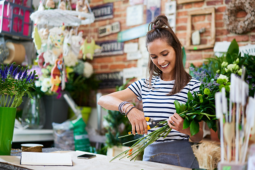 Cheerful young florist cutting flowers for bouquet at the counter