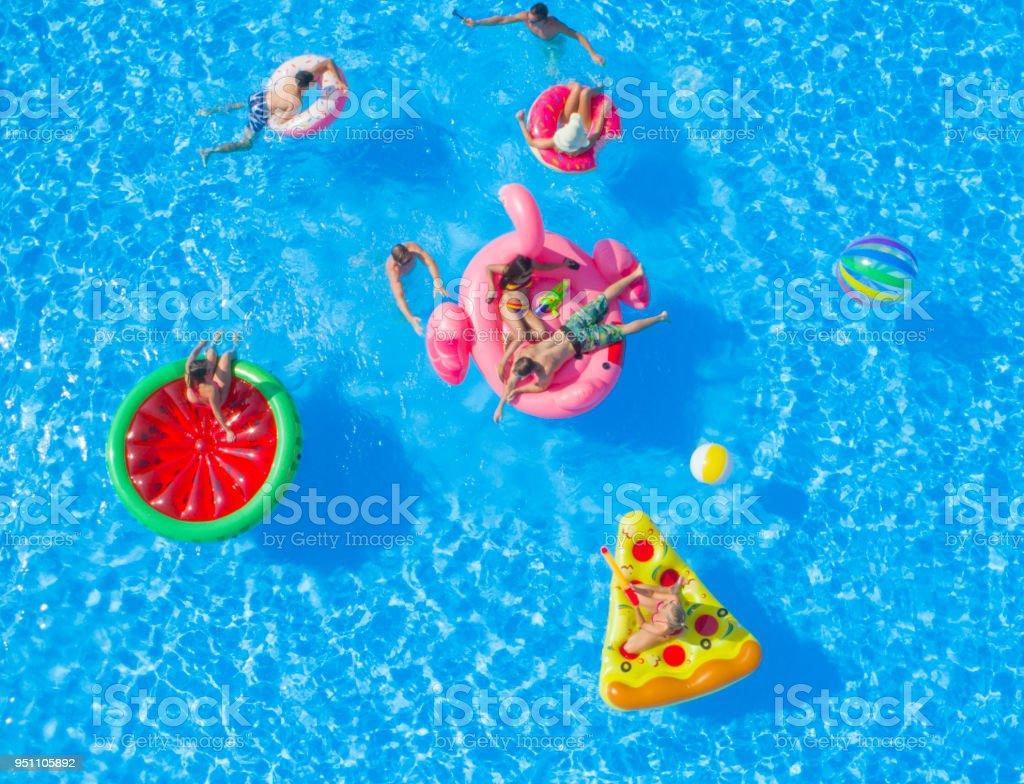 AÉREA: Alegres jovens amigos tendo uma watergun lutam na boia na festa da piscina - foto de acervo