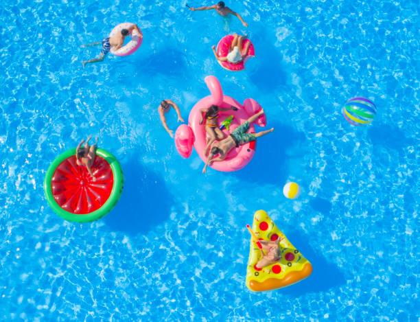 antenn: glada unga vänner som har en watergun slåss på floaties på poolparty - flotte bildbanksfoton och bilder