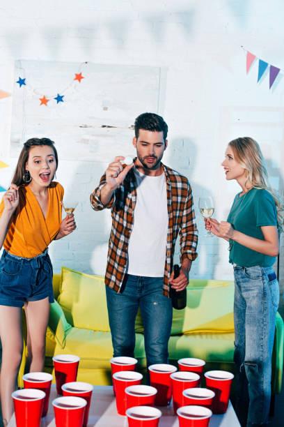 fröhliche junge freunde, spaß haben und spielen bier pong zu hause feiern - lustige trinkspiele stock-fotos und bilder
