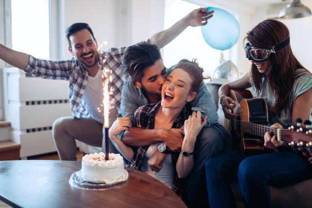 fröhliche junge freunde, die spaß auf party - gitarren geburtstagstorten stock-fotos und bilder