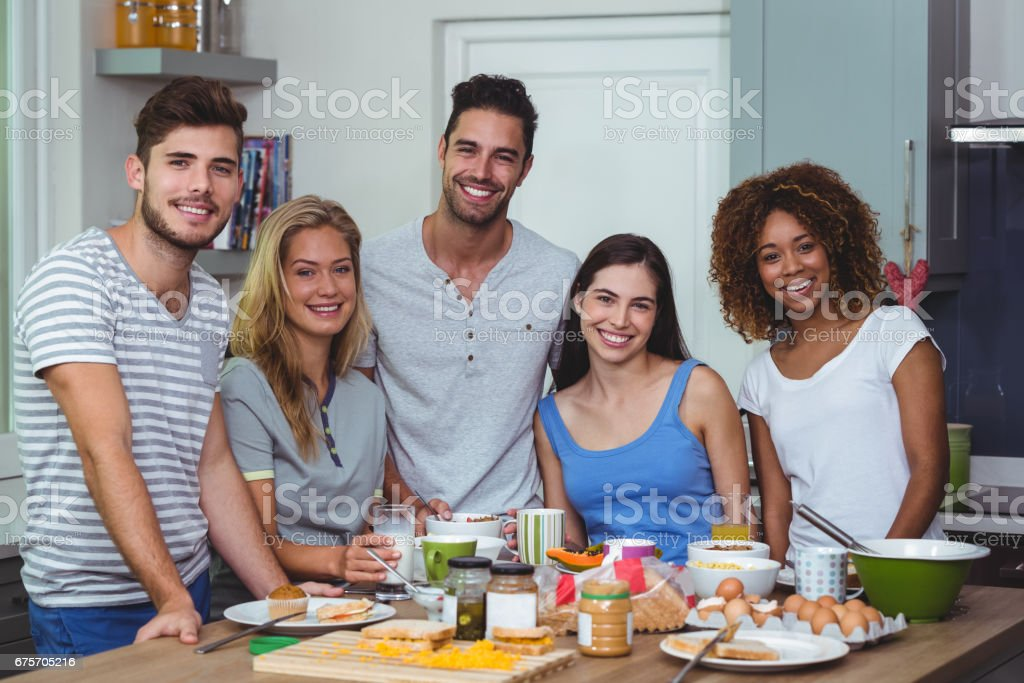 Cheerful young friends standing at table royalty-free stock photo