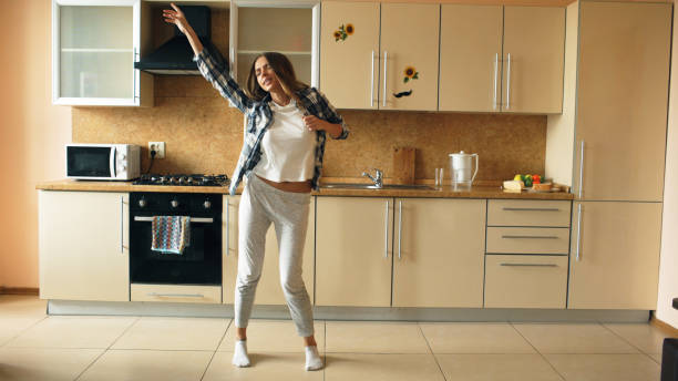 Cheerful young funny woman dancing and singing with ladle while having leisure time in the kitchen at home stock photo