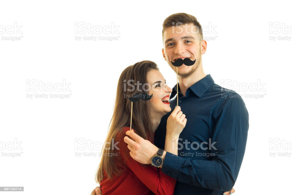 cheerful young girl and Guy are holding paper black whiskers stock photo