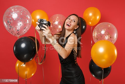 istock Cheerful young girl in black dress doing taking selfie shot on retro vintage photo camera on bright red background air balloons. Valentine's Day, Happy New Year, birthday mockup holiday party concept. 1132758406