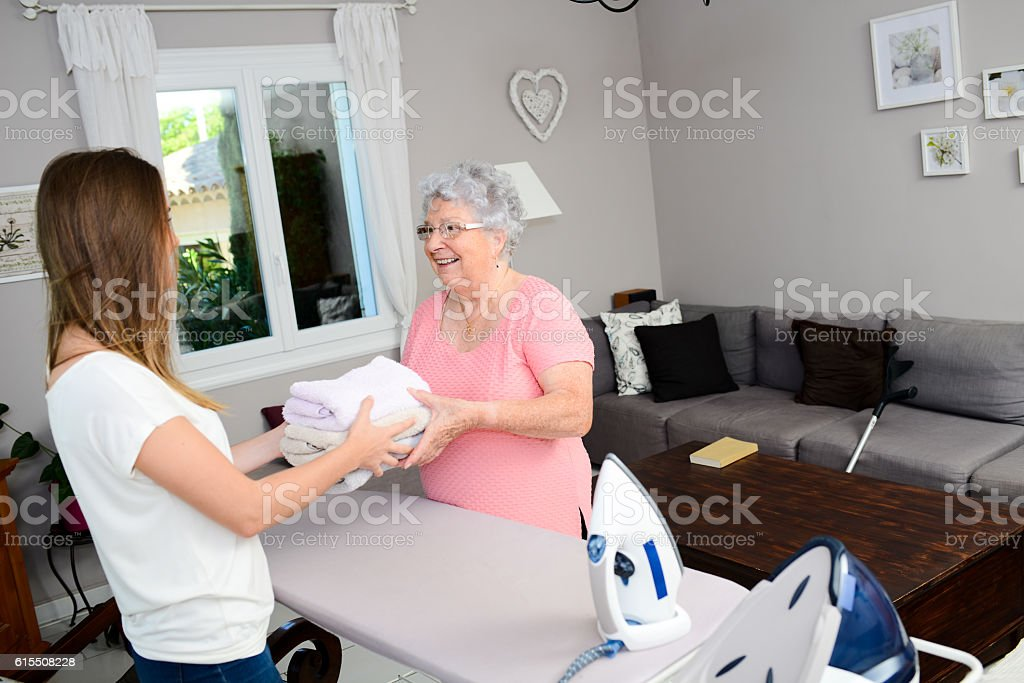 cheerful young girl ironing and helping elderly woman at home stock photo