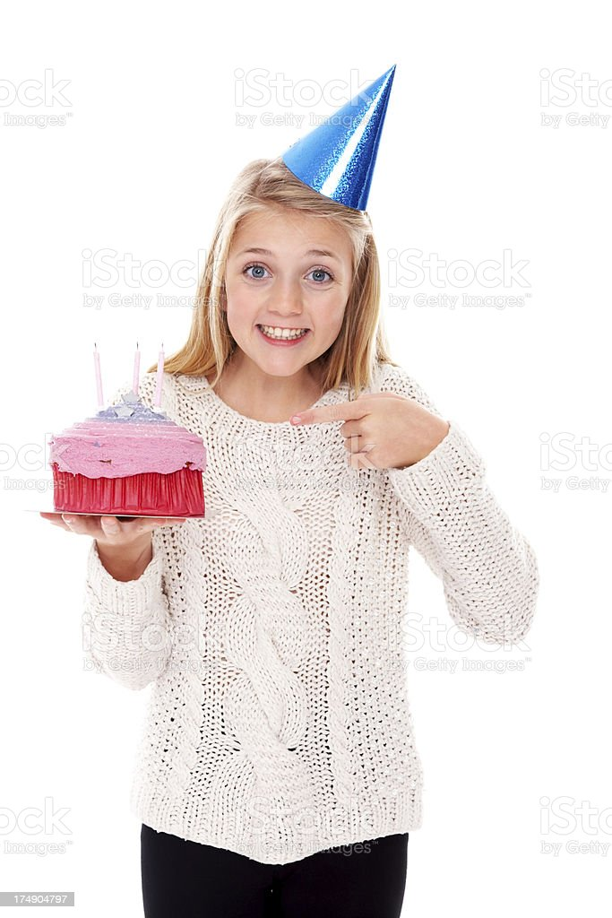 Cheerful young girl pointing at birthday cake in her hand royalty-free stock photo
