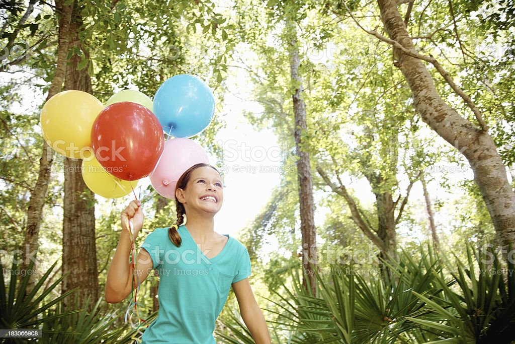 Cheerful young girl running with colorful balloons in a park royalty-free stock photo