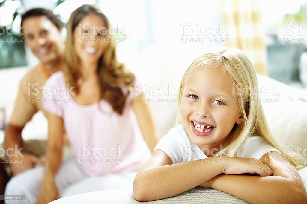 Cheerful young girl with blurred parents in background royalty-free stock photo