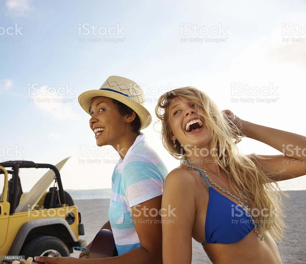 Cheerful young girl with her friend playing guitar on beach royalty-free stock photo