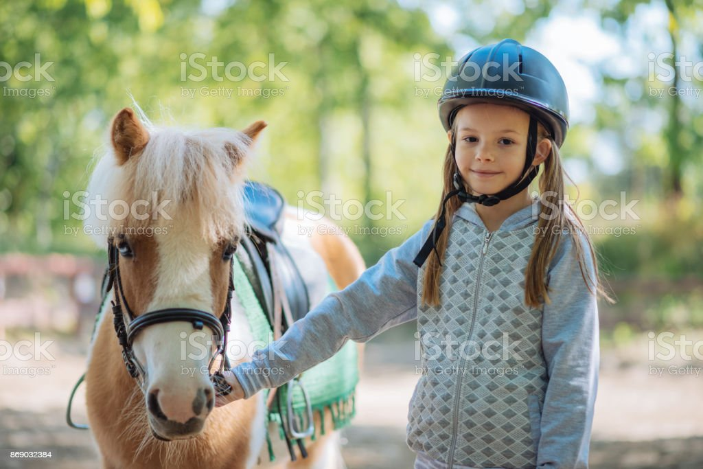 Cheerful young girl with her pony horse stock photo