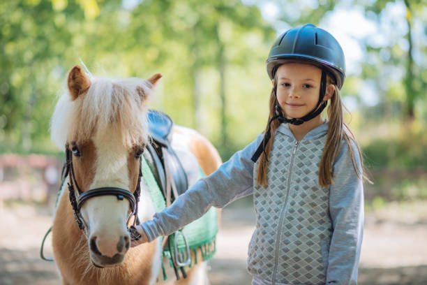 Cheerful young girl with her pony horse Kids with their pony horses on dressage. Kids with their personal trainer learn horseback riding. Great recreation for kids age 4 to 7, before they get on the big horses. pony stock pictures, royalty-free photos & images