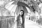 Cheerful young Indian teenage girl standing in the nature with  umbrella during summer sunny day outdoors.