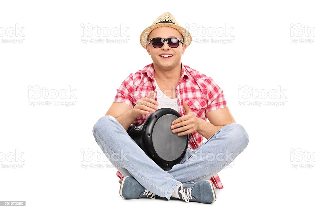 Cheerful young guy playing a doumbek stock photo