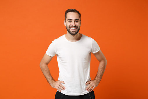 Cheerful young handsome man in casual white t-shirt posing isolated on orange wall background studio portrait. People sincere emotions lifestyle concept. Mock up copy space. Standing with arms akimbo.