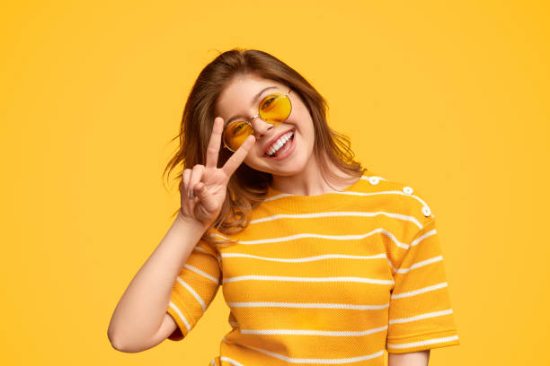 Cheerful young hipster gesturing V sign stock photo