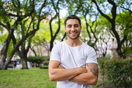 Handsome young Hispanic man enjoying the day in a public park in summer.